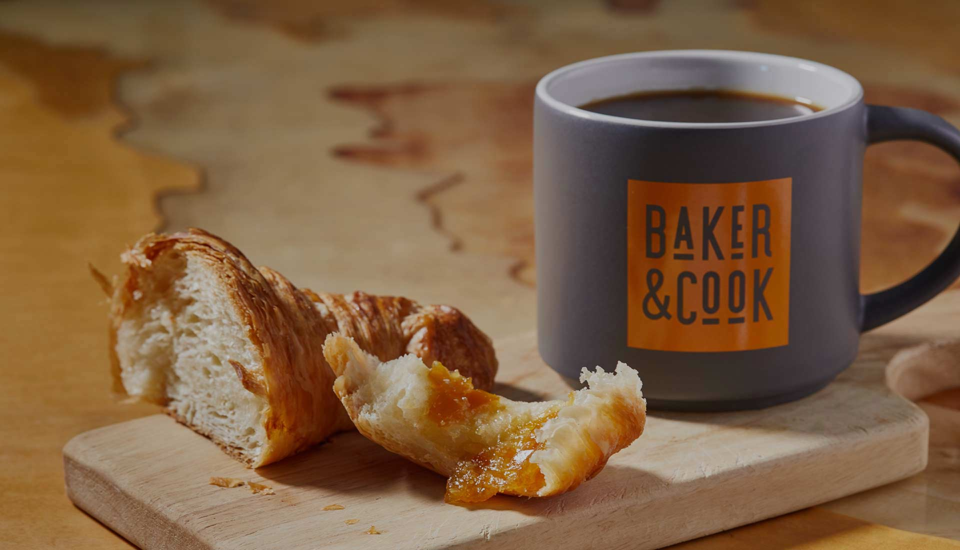 croissant next to a cup of coffee from Baker & Cook